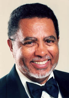 African American composer Adolphus Hailstork, wearing a black tuxedo, against an ivory colored background