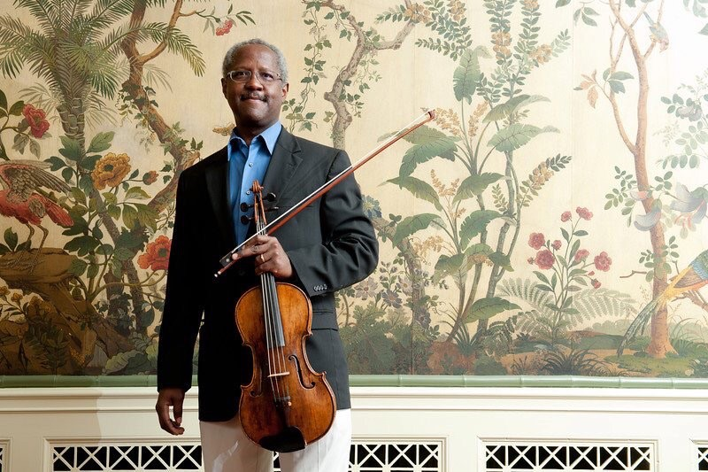 African American violist George Taylor, wearing a robin's egg blue button down shirt, navy suit coat and holding his viola, stands against a colorful wallpapered wall.