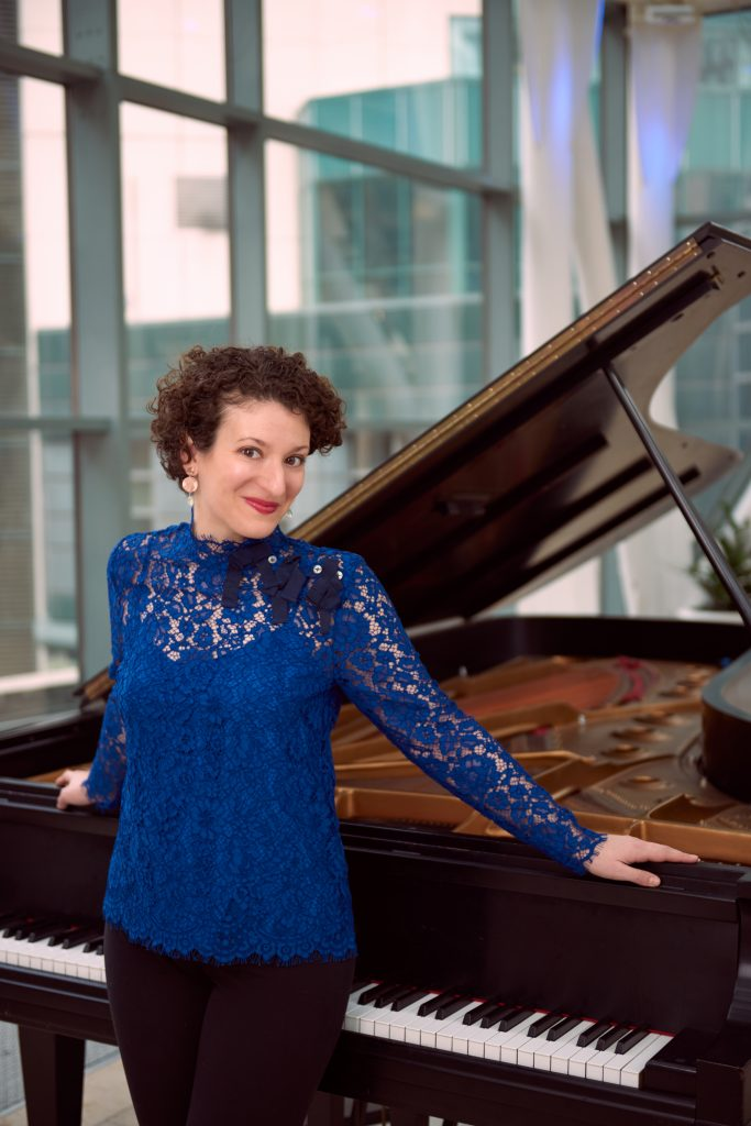 A woman with curly hair wearing a royal blue long sleeved lace top leans against an open black grand piano