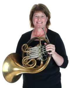 A smiling woman, wearing all black, holds a brass French horn